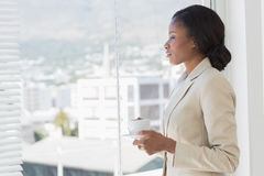 Elegant businesswoman with tea cup looking through office window Royalty Free Stock Photo