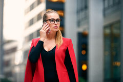 Elegant businesswoman walk in city financial district and talking on cell phone wearing jacket and eyeglasses Royalty Free Stock Image