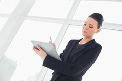 Elegant businesswoman writing notes in office Royalty Free Stock Image