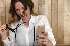 Elegant businesswoman writing text with a smartphone in a restau Stock Images