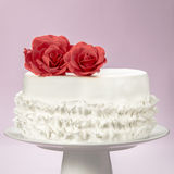 Elegant Cake and Sugar Red Roses on the Top. An elegant and white fondant cake with artisanal sugar red roses on top Royalty Free Stock Images