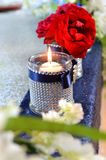 Elegant Candle and Flowers. On table stock photo