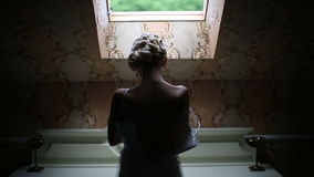 Elegant caucasian bride wears a wedding dress standing at the window stock video footage