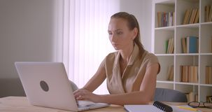 Elegant caucasian businesswoman analyzing data on laptop turns to camera and smiles pleasantly in office. Elegant caucasian businesswoman analyzing data on stock footage