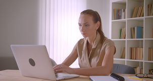 Elegant caucasian businesswoman analyzing data on laptop turns to camera and smiles prettily in office. Elegant caucasian businesswoman analyzing data on laptop stock video
