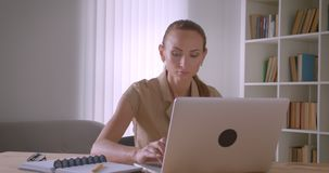 Elegant caucasian businesswoman analyzing data on laptop turns to camera and watches seriously in office. Elegant caucasian businesswoman analyzing data on stock video