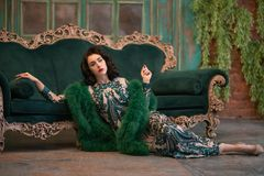 Elegant caucasian girl in a luxurious long sequins lace dress with a green fluffy boa in her hands posing in the retro room with v stock photography