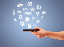 Hand holding tablet phone with drawn icons. An elegant caucasian white hand holding mobile phone with drawn social media icons in front of an empty clear blue Stock Photos