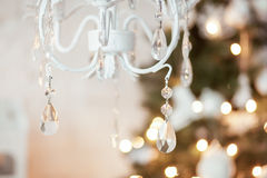 Elegant chandelier in the background Christmas decorations, garlands, xmas tree. interior in white and gold colors.  Royalty Free Stock Photography