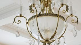 Elegant chandelier hanging under the ceiling Royalty Free Stock Photography