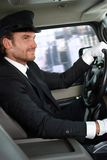 Elegant chauffeur driving luxurious car Stock Photography