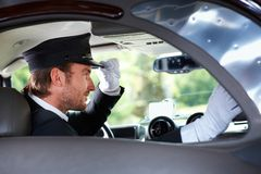 Elegant chauffeur in luxurious car stock photo