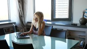 Elegant and cheerful woman. Cheerful young beautiful woman looking at laptop with smile while sitting at table in her stock video