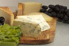 Elegant cheese display on a wooden serving board Royalty Free Stock Photo