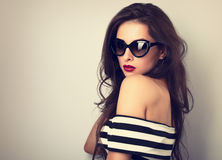 Elegant chic female model with long hair posing in fashion sunglasses in striped dress on toned color background. Closeup royalty free stock images