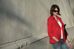 Elegant and chic young french woman. Wearing a red jacket leaning against a wall Stock Photography