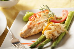 Elegant chicken. Deliciously grilled chicken breast with a sprig of rosemary, asparagus and a fork Royalty Free Stock Photos