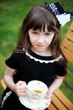 Elegant child girl having a tea party outdoors Stock Images