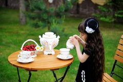 Elegant child girl having a tea party outdoors Stock Photography