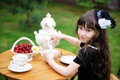 Elegant child girl having a tea party outdoors Stock Image