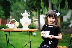 Elegant child girl having a tea party outdoors Royalty Free Stock Photos