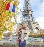 Elegant child rising flag while sitting on the parapet in Paris Royalty Free Stock Image