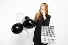 Elegant chockad flicka, i svart klänning, med shoppingpåsar och bla arkivbild