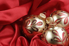 Elegant Christmas Background. Gold and red ornaments on a background of rich red satin. Horizontal presentation stock image