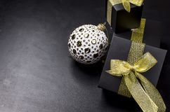 Elegant Christmas background with white retro balls and gifts. Beautiful white and golden christmas ball and black gift box with gold ribbon on a black stock photo
