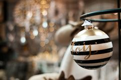 Elegant Christmas bauble with Joy word and bokeh. An elegant black and white striped Christmas baubble with joy word and shiny lights bokeh as copyspace stock photos