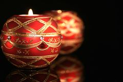 Elegant Christmas Candles. Gold and red glass candles on dark background with reflection Royalty Free Stock Photos