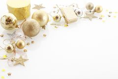 Elegant Christmas corner border. With golden gifts, baubles, stars in a decorative arrangement over white with copyspace for your seasonal greeting Royalty Free Stock Photography