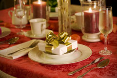 Elegant Christmas table setting in red. With gold gift as focal point Stock Photo