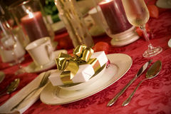 Elegant Christmas table setting in red. And gold colors, gift as focal point Stock Image