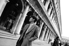 Elegant chinese man walking in street in Venice. Italy stock images