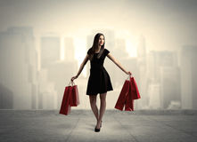 Elegant city girl with red shopping bags Royalty Free Stock Images