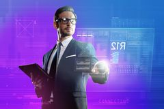 Elegant clever man holding a smartphone while using transparent computer. Smart man. Calm experienced elegant programmer wearing glasses and holding a convenient Stock Photography