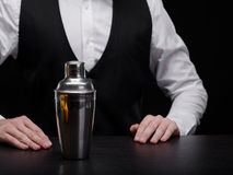 Bartender with shaker. Professional barman in a suit with a shaker on a black background. Cocktail preparation concept. Elegant club bartender in a professional stock image
