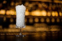 Elegant cocktail glass for Sherry Cobbler filled with ice on the. Bar counter against the bright golden light royalty free stock image