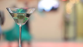 Elegant cocktail party with tango dancers. Cocktail glass in foreground at an elegant party with tango dancers in background stock video footage