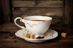 Elegant coffee cup with beans and sugar cubes Royalty Free Stock Images