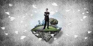 Confident boss and modern city as concept of eco green construct. Elegant confident businessman standing on green floating island against concrete background stock illustration
