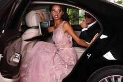 Elegant couple arrived on red carpet event in luxurious car. Fashion photo of gorgeous mulatto women with long dark hair wears luxurious dress and men in elegant stock photos
