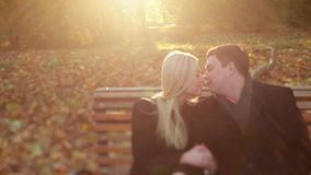 Elegant couple in autumn wear, gorgeous young blonde girl and handsome man. Young lovers sitting on the bench in autumn. Park and tenderly kissing in a bright stock video footage