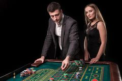 Elegant couple at the casino betting on the roulette, on a black background Royalty Free Stock Images