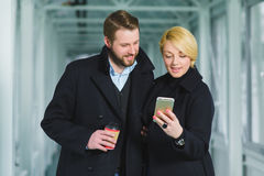 Elegant couple dressed in coat looking on smart phone at lobby Stock Images