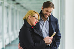 Elegant couple dressed in coat looking on smart phone at lobby Stock Photography