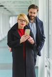 Elegant couple dressed in coat looking on smart phone at lobby Stock Image