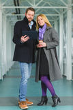 Elegant couple dressed in coat looking on tablet Stock Photo