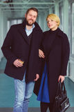 Elegant couple dressed in coat standing at lobby Royalty Free Stock Photo